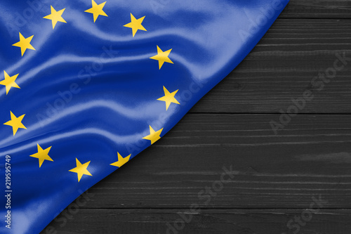 Foto  Flag of the European Union and place for text on a dark wooden background
