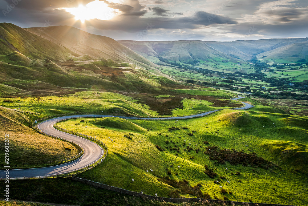 Fototapeta Sunset at Mam Tor, Peak District National Park, with a view along the winding road among the green hills down to Hope Valley, in Derbyshire, England.