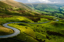 Sheep At Mam Tor, Peak District National Park, At Sunset, With A View Along The Winding Road Among The Green Hills Down To Hope Valley, In Derbyshire, England.