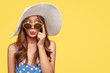 Stylish woman with surprised mysterious expression, looks asdie, wears stylish summer shades, hat and polka dot blouse, isolated over yellow background with copy space for your text. Relaxation