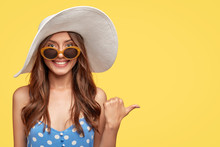 Summer Time Concept. Cheerful Beautiful Brunette Woman In Stylish Sunglasses And Hat, Has Friendly Smile, Points With Thumb Aside, Shows Blank Space For Your Advertisement Or Promotional Text
