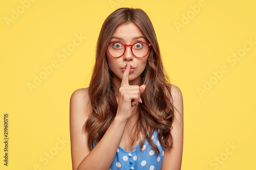 Photo  Horizontal shot of attractive young female shows silence sign, asks to be close