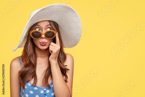 Fototapeta Stylish woman with surprised mysterious expression, looks asdie, wears stylish summer shades, hat and polka dot blouse, isolated over yellow background with copy space for your text. Relaxation obraz