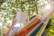 Reading At Dusk In The Hammock With The Open Book