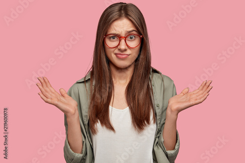 Uncertain indignant puzzled student forgets information during exam, shruggs shoulders and clasps hands with hesitation, looks clueless, isolated over pink background Wallpaper Mural