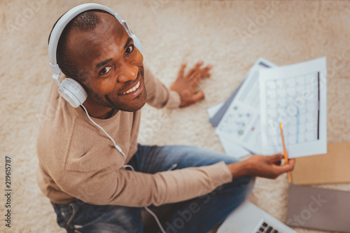 Staande foto Ontspanning Great day. Inspired afro-american man sitting on the floor and listening to music