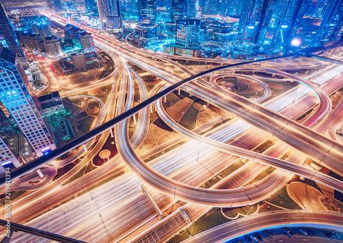 Fototapeta premium Widok z lotu ptaka na duże skrzyżowanie autostrad z ruchem w Dubaju, Zjednoczone Emiraty Arabskie, w nocy. Malowniczy pejzaż. Kolorowe tło transportu, komunikacji i jazdy.