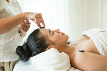 Obraz na płótnie Canvas Beautiful woman lying in spa salon and enjoying face massage, Health care concept.