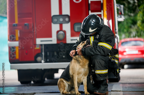 Photo of fireman squatting next to service dog near fire engine Canvas Print