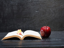 Frangipani Flower And Red Apple And Book On Wooden Desk