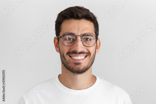 Obraz Daylight portrait of young handsome caucasian man isolated on grey background, dressed in white t-shirt and round eyeglasses, looking at camera and smiling positively - fototapety do salonu