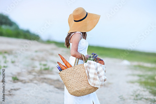 Young woman holding picnic basket with bottle of wine and baguette