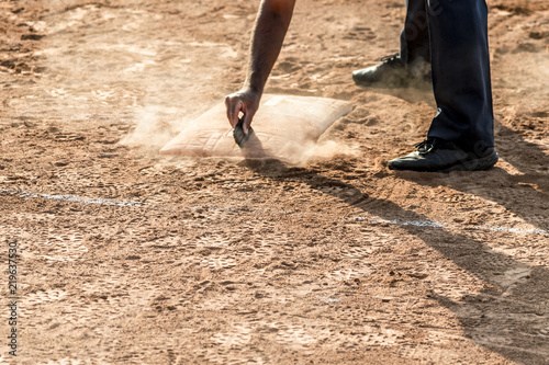 Referee cleans home plate in a baseball (softball) dusty field, with copyspace
