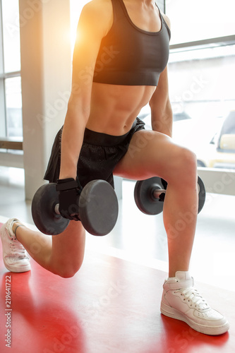 Valokuvatapetti close up dumbbell lunge blonde woman with earphones workout exercise at gym, one