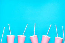 Row Of Pink Empty Paper Cups Striped Drinking Straws Arranged In Bottom Border On Mint Blue Background. Creative Flat Lay. Birthday Party Celebration Kids Baby Shower. Pastel Colors. Poster Banner