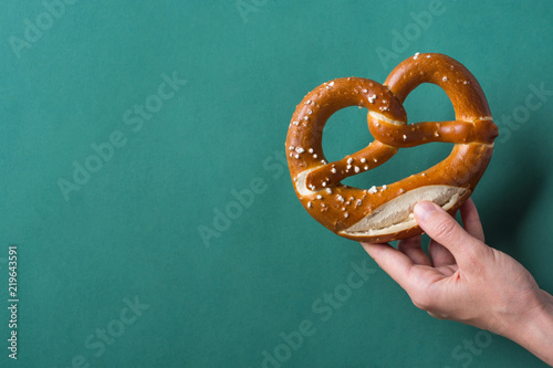Fotografie, Obraz  Young woman hold in hand German savory lye pretzel with salt on dark green background