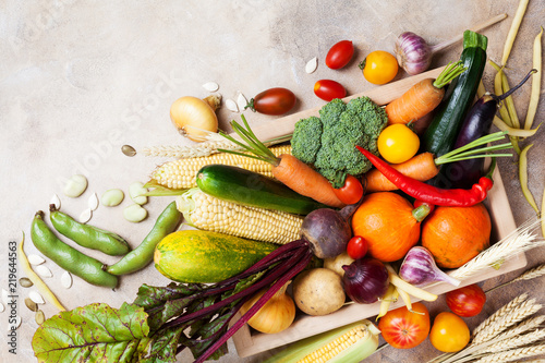 Autumn harvest farm vegetables and root crops on wooden box top view. Healthy food background.
