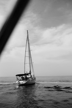 Black And White Shot Of Retreating Sailing Boat With Sails Down In Sea Horizon