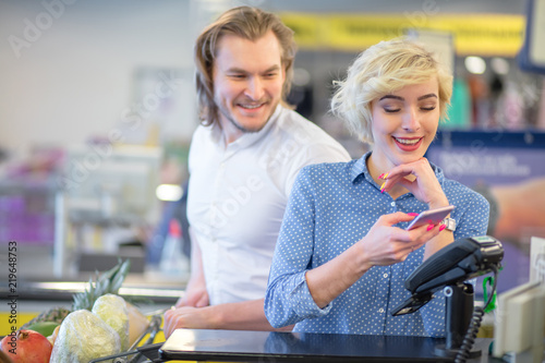 Fotografía  Young couple bying goods in city mall, blonde pretty woman shows her coupons at