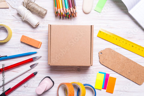 Cardboard box and stationery on wooden background, top view