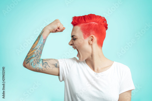 crazy girl is shouting during workout. close up side view photo. isolated blue background.hard training. funny fit girl isn't satisfied with her muscles