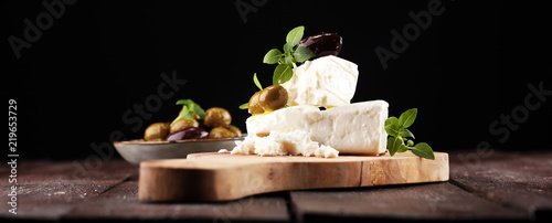 Fototapeta Greek cheese feta with herbs and olives on rustic table. obraz