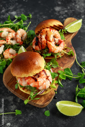Healthy Tasty prawn grilled burger with pea shoots and sweet chilli dip served on wooden board with lime wedges