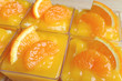 Many Vibrant Color Mandarin Orange Cakes in Glass Bowls Topped with Fresh Oranges