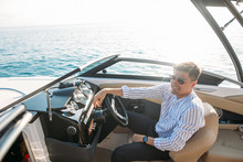 Handsome Smiling Young Man Customer In Classy Pants And Shirt, Examines Boat Steering Panel And Checks The Move Of A Motor Boat Before Buying It