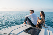 Attractive Caucasian Couple Sunbathing On A Motor Boat Enjoying Marine Trip Along Sea Coast. Perfect Celebration Of A Honeymoon With Great Beautiful Seascapes With Copyspace For Message