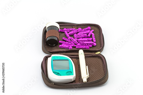 Fotografía  blood glucose meter, the blood sugar value is measured on a finger pack in black case on white background