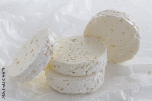 Feta cheese rounds close up on white parchment paper background