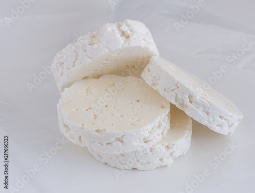 Feta cheese rounds stacked on white parchment paper