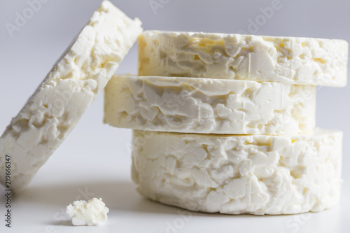 Feta cheese round disk stack close up side view isolated  on white background