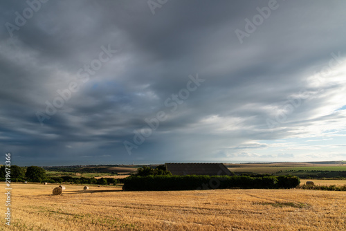 Beautiful Summer landscape of field of hay bales with dramatic stormy clouds overhead in English countryside