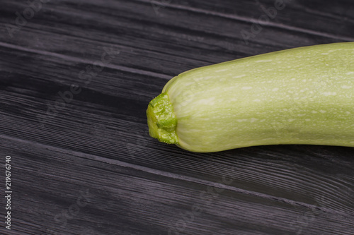 Bright courgette close up. Dark black wooden table background.