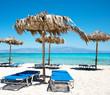 Two Deckchairs Under Parasol In Tropical Beach at quiet sea