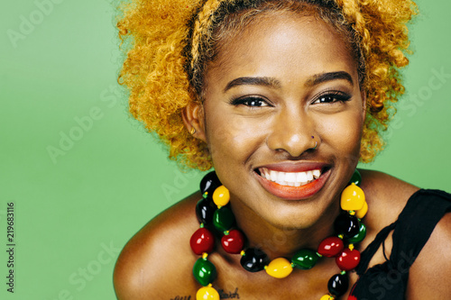 Fotografie, Obraz  Close up of a very happy young girl with big smile and colorful necklace, in fro