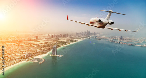 Private jet plane flying above Dubai city in beautiful sunset light.