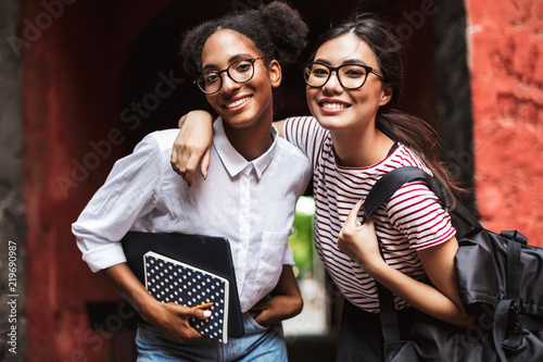 Fényképezés  Two pretty smiling girls in eyeglasses with laptop and backpack happily looking