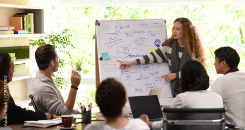 Photographie  Young business woman giving presentation on future plans to his colleagues at of
