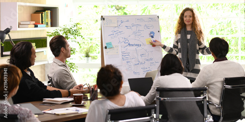 Fotomural  Young business woman giving presentation on future plans to his colleagues at of