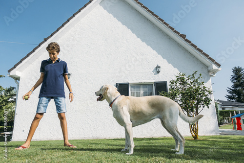 Handsome guy poses with pet together white wall of house