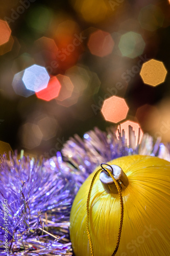 Fototapety, obrazy: Yellow glass ball lie in Christmas tinsel. On New Year's toys painted gold heart. In the background, blurred lights of a Christmas tree. Bokeh background.