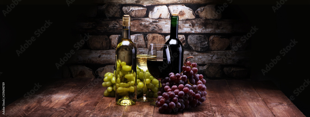 Red Wine bottle and white wine with grapes and glasses on wooden background