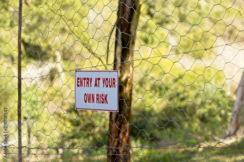 Photo An ENTER AT YOUR OWN RISK warning sign hanging on a boundary fence
