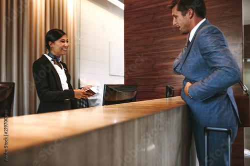 Cuadros en Lienzo Businessman checking in at hotel reception