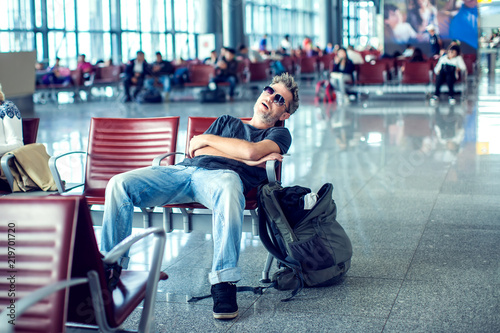 Fotografía  Man sleeping while sitting in airport terminal and waiting for flight departure