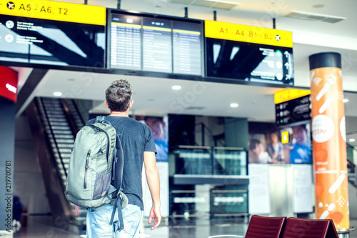 Fotografering  A young male traveler with a backpack looks at the information board at the airport