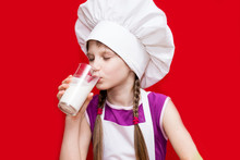 Portrait Of Beautiful Little Girl In Form Of Cook Isolated On Red Drink Milk. Kid Chef. Healthy Habits